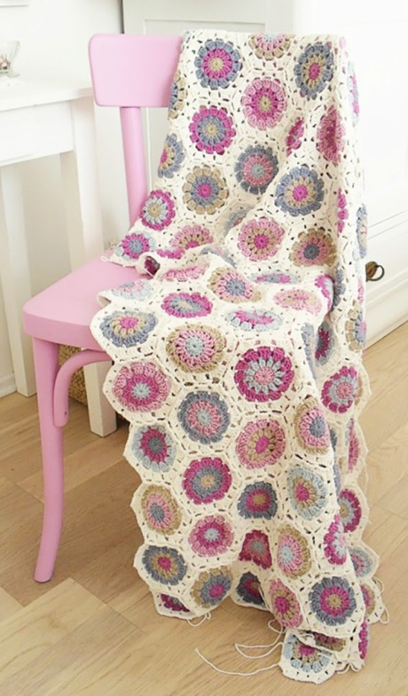 crochet blanket on pink wooden chair